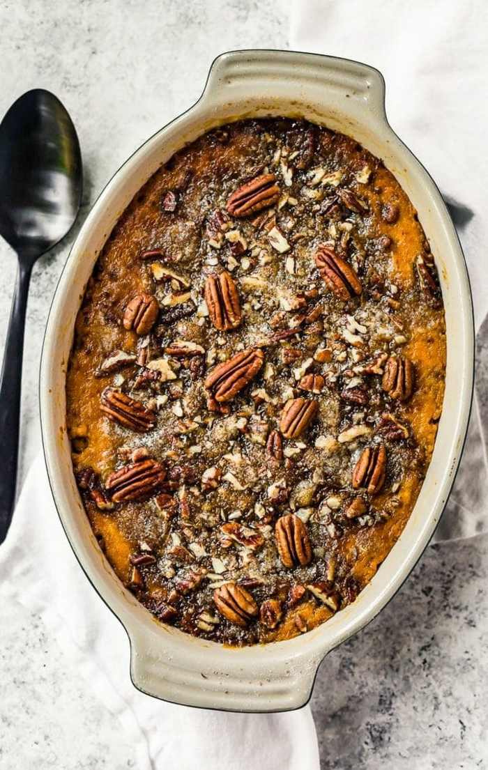 sweet potato casserole with pecans on top, baked in ceramic casserole dish, spoon on the side, easter dishes