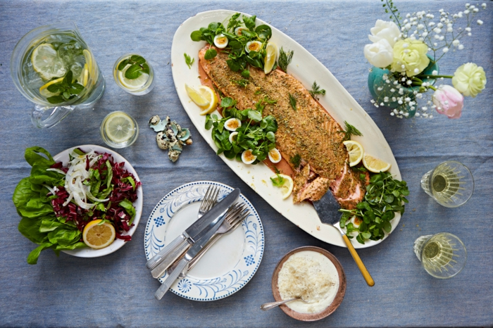 easter dinner menu ideas, table with blue table cloth on it, baked salmon placed on white plate, green herbs on the side