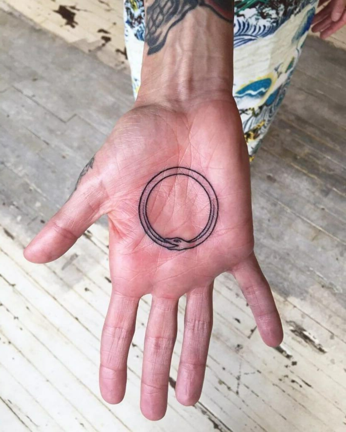 tattoo on the palm of the hand, snake eating its own tail, white wooden floor in the background