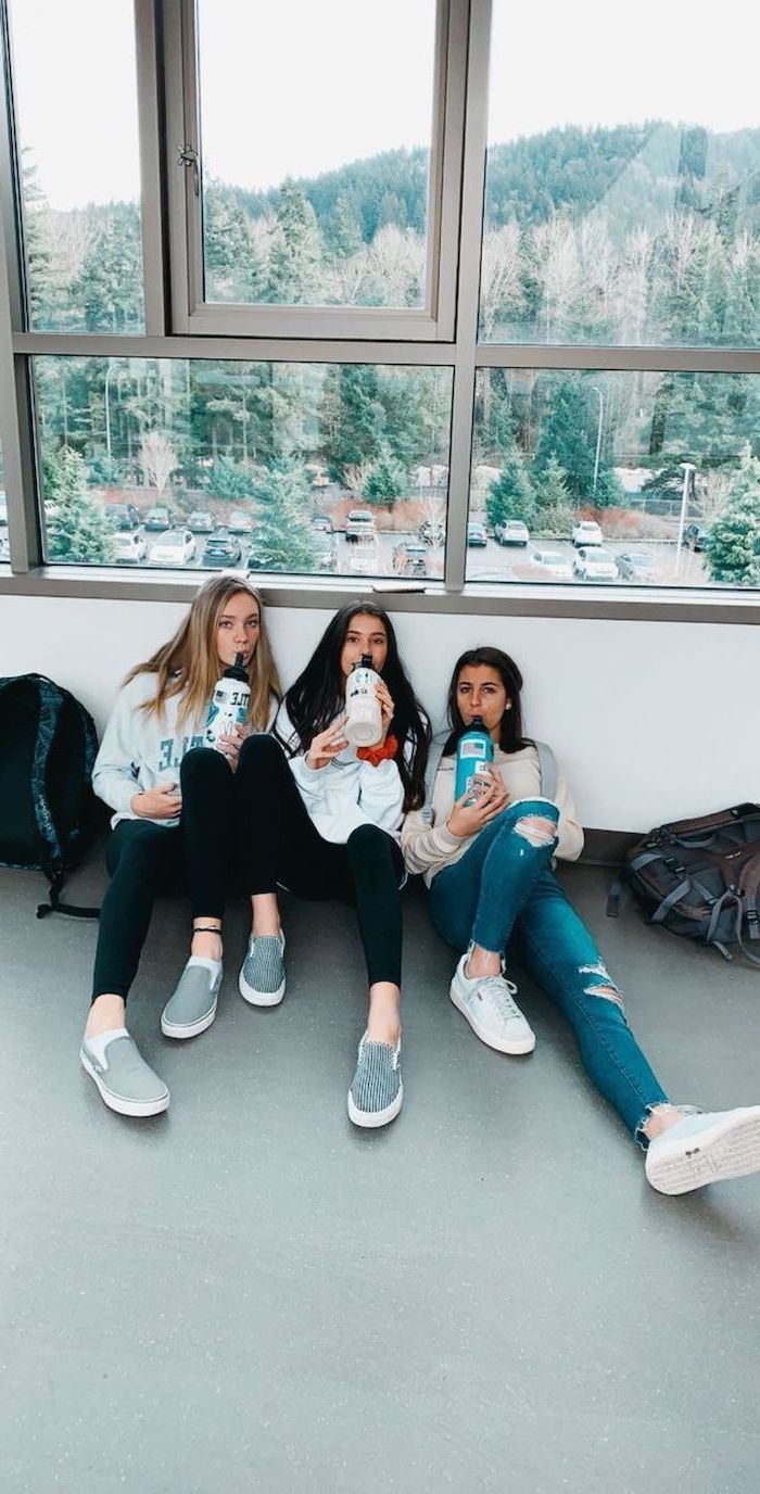three girls sitting on the floor, wearing jeans and sweatshirts, cute high school outfits, white and grey vans shoes
