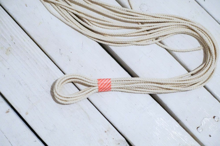 three strands of macrame, held together with tape, placed on white wooden surface, how to make a macrame plant hanger