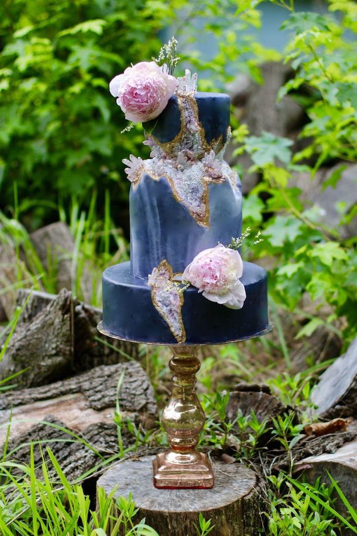 three tier cake, covered with blue marble fondant, decorated with purple rock candy and flowers, geode birthday cake