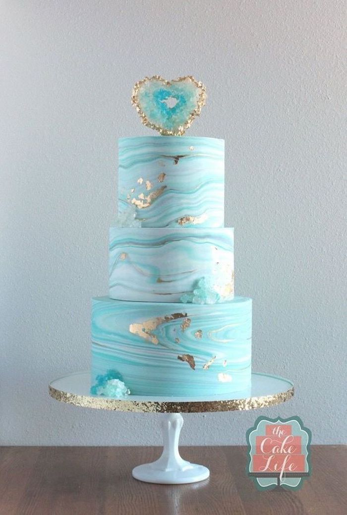 three tier cake, covered with blue and white marble fondant, decorated with turquoise rock candy, pink geode cake