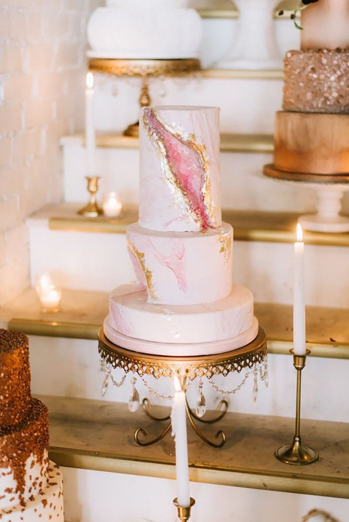three tier cake, covered with pink marble fondant, pink geode cake, decorated with pink rock candy, placed on gold cake stand