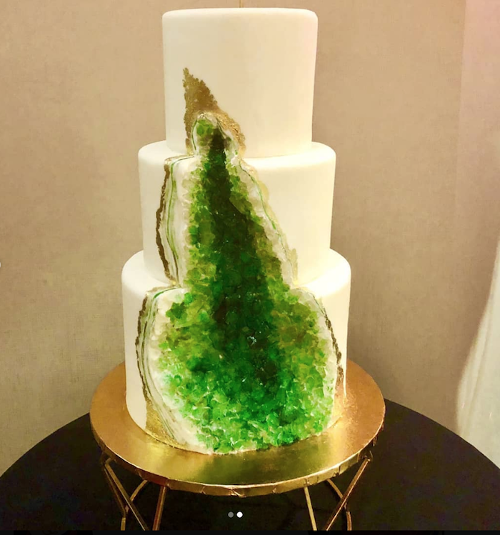 three tier cake, covered with white fondant, pink geode cake, decorated with green rock candy, placed on gold cake stand