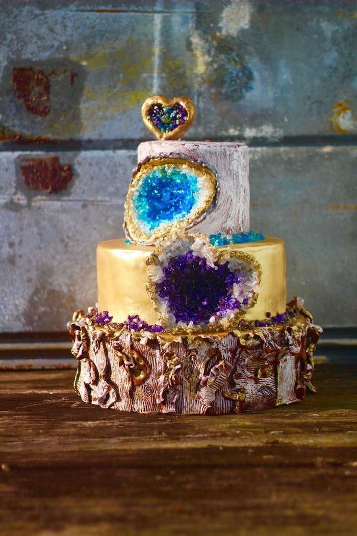 three tier cake, covered with white and gold fondant, decorated with turquoise and purple rock candy, pink geode cake