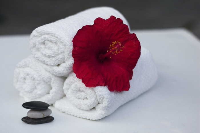 three white towels stacked together, red flower on top of them, spa holidays, three rocks stacked together, all placed on white surface