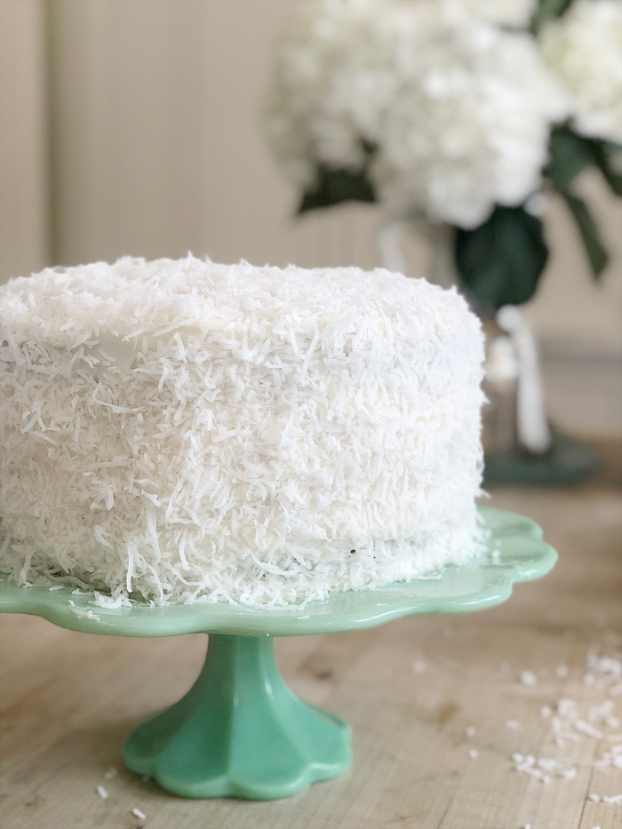 one tier cake, covered with coconut flakes, palced on turquoise cake stand, easter dinner menu ideas