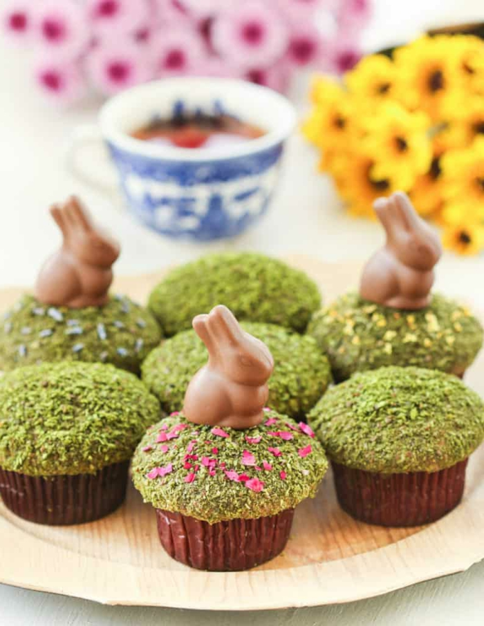 cupcakes with matcha powder on top, small chocolate bunnies cupcake toppers, easter dinner menu ideas, wooden plate