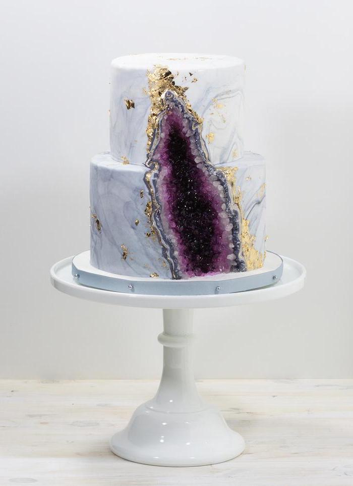 two tier cake, covered with white and grey marble fondant, pink geode cake, decorated with purple rock candy