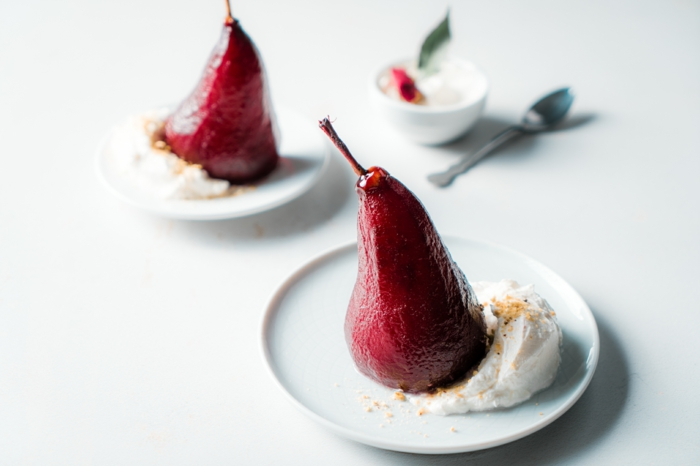 poached pears in red wine, served with cream on white plates, placed on white countertop