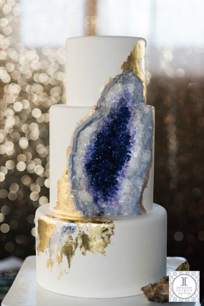 three tier cake, covered with white fondant, what is a geode cake, decorated with white and purple rock candy