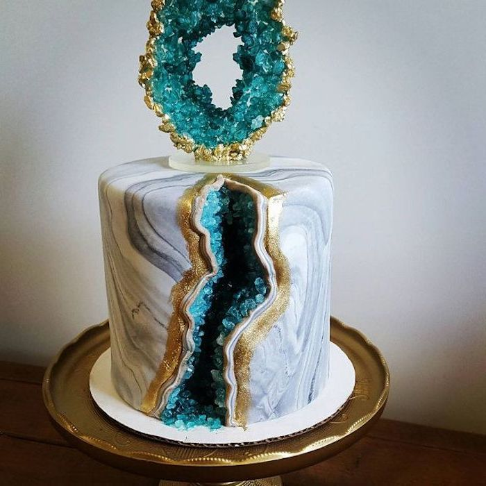what is a geode cake, one tier cake, covered with white and grey marble fondant, decorated with turquoise rock candy