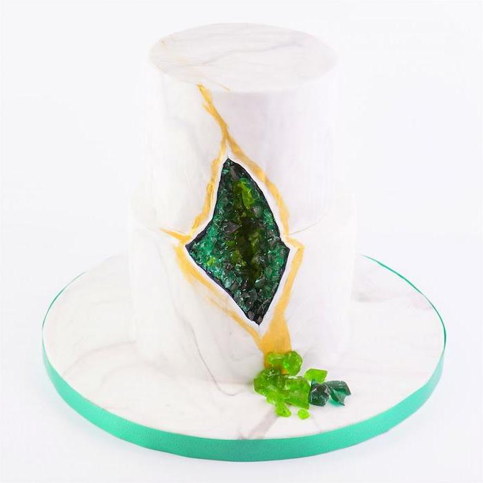 two tier cake, covered with white fondant, what is a geode cake, decorated with green rock candy and gold paint