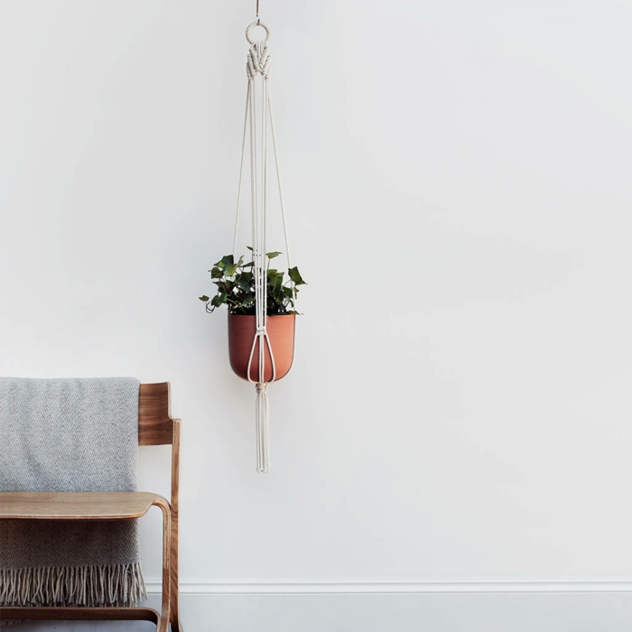how to make a macrame plant hanger, ceramic pot hanging from the ceiling, next to a wooden chair with throw blanket