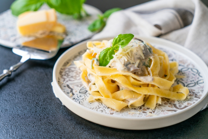 black surface, tagliatele recipe, white plates, garnish of creamy mushroom sauce, parmesan cheese and basil leaves