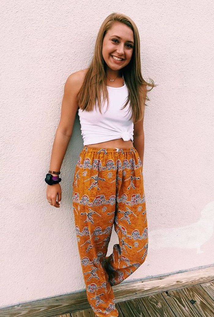 girl leaning on white wall, wearing orange wide fit pants, cute lazy outfits, white crop top