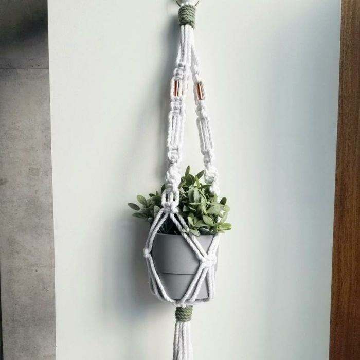grey ceramic pot with plant inside, hanging on white wall, easy macrame plant hanger