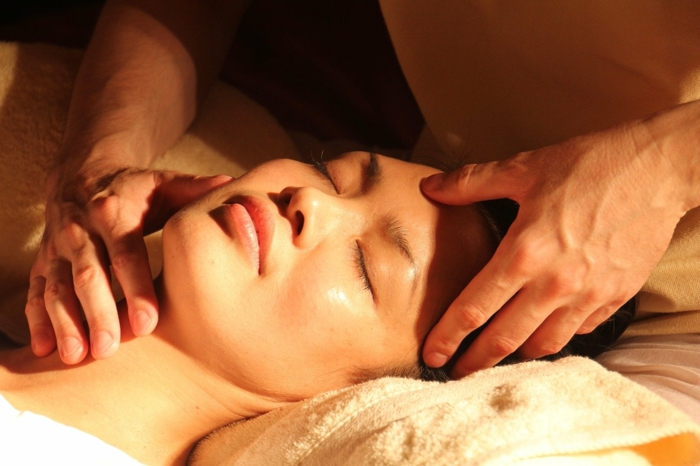 woman laying on a bed with closed eyes, white towel under hear head, spa holidays, getting a massage