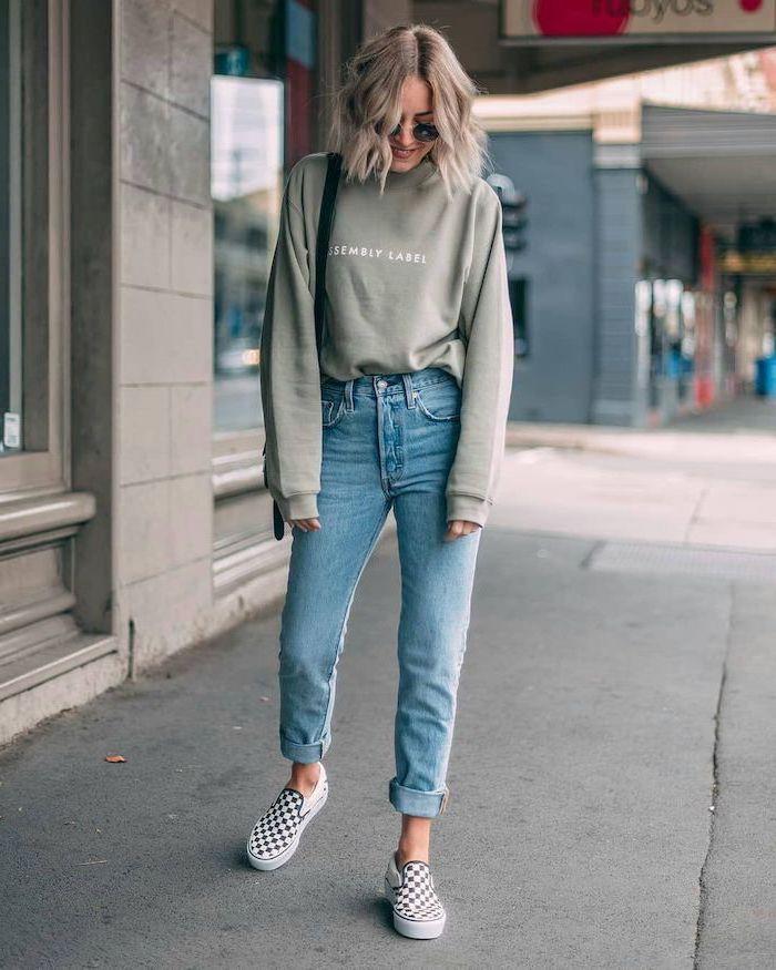 blonde woman walking on sidewalk, wearing jeans and grey sweatshirt, cute winter outfits for school, vans shoes