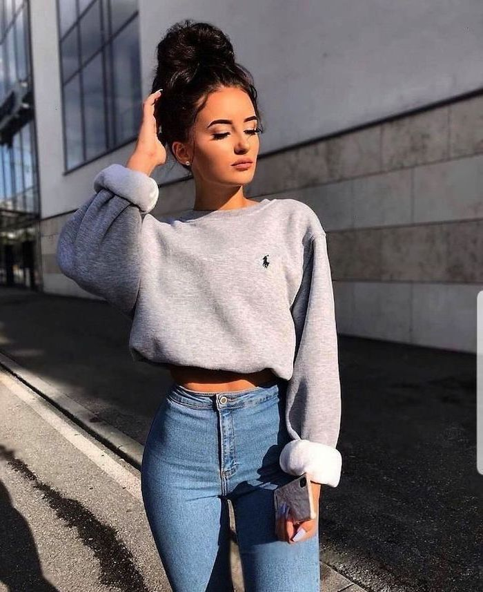 cute winter outfits for school, woman with black hair in a bun, wearing jeans and grey sweatshirt