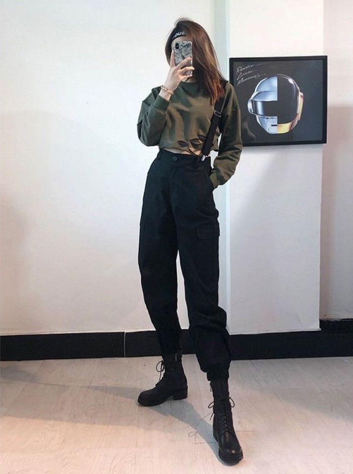 brunette girl wearing olive green crop top, black trousers with black suspenders, cute winter outfits for school, black leather boots