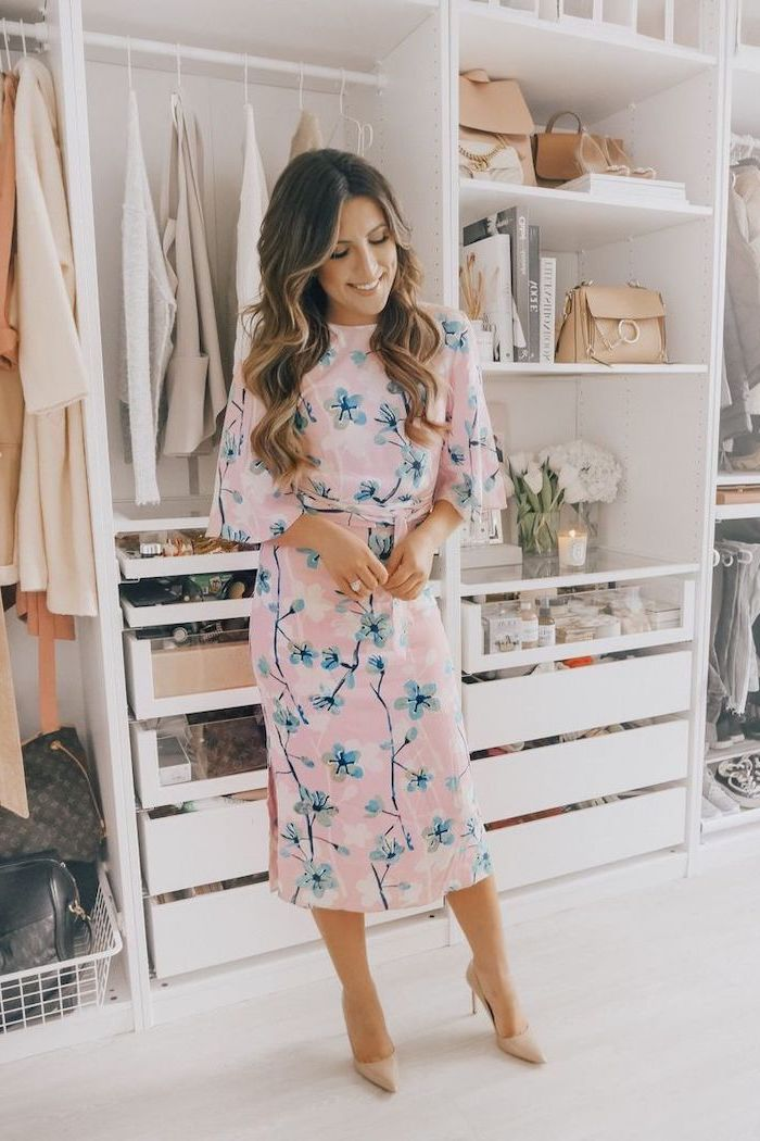 woman standing in a large closet, cute spring dresses, wearing a pink dress with floral print, nude heels
