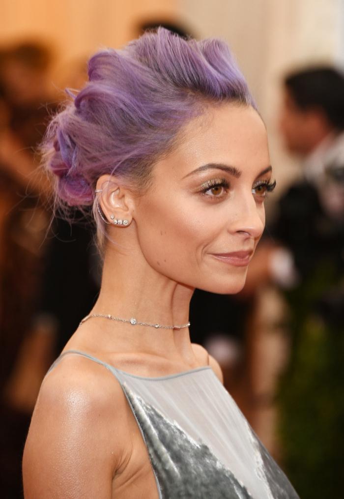 nicole richie, purple hair in a low updo, wearing silver velvet dress, stud cartilage piercing, multiple earrings