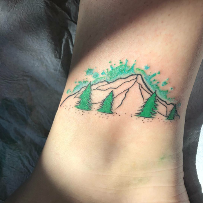 mountain range tattoo, watercolor ankle tattoo, mountain range with green trees, turquoise sky