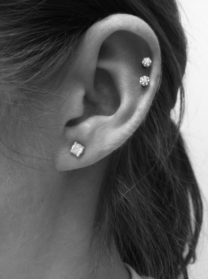 black and white photo, close up of an ear, multiple earrings with rhinestones, helix piercing