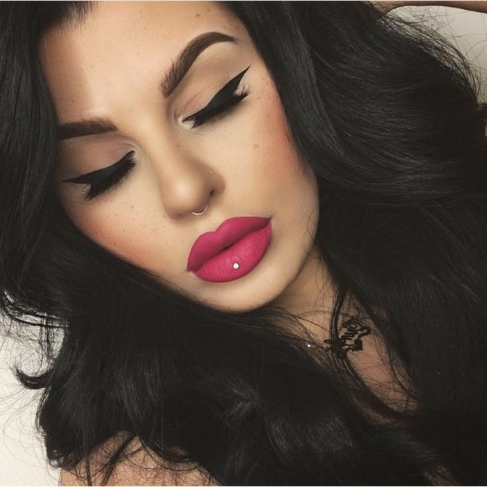 woman with black hair, bottom lip piercing, pink matte lip gloss, black eyeliner and long eyelashes