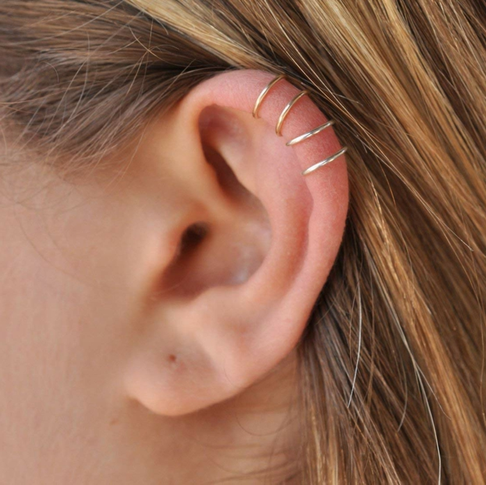 blonde woman, close up photo of her ear, double cartilage piercing, four golden ring earrings