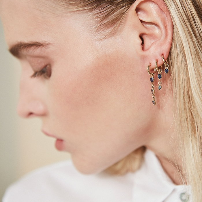 woman with blonde hair, photo of her ear, double helix piercing, wearing three earrings with blue rhinestones