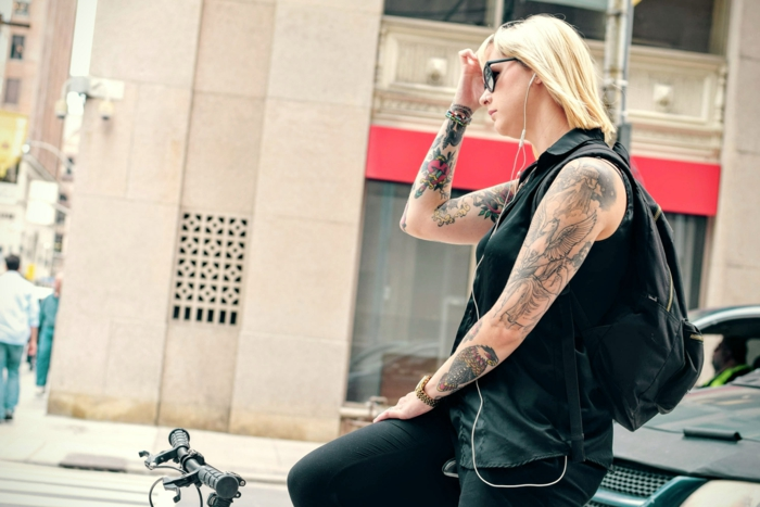 neo traditional tattoo, blonde woman riding a bike, wearing all black, arms covered with tattoos