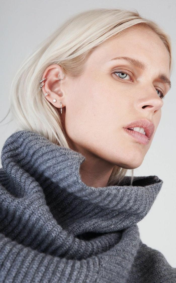 blonde woman with blue eyes, wearing grey turtleneck sweater, double cartilage piercing, multiple earrings