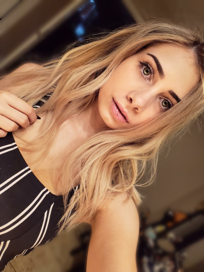ashley piercing, girl with blonde wavy hair and green eyes, wearing black and white striped top