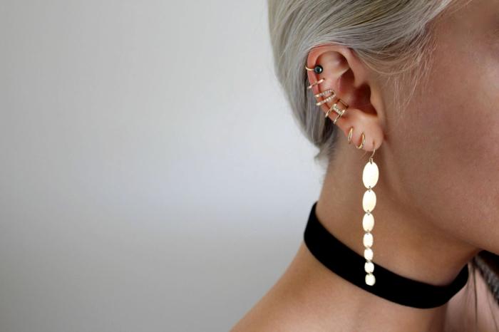 blonde woman, wearing black velvet choker, multiple earrings on her ear, double cartilage piercing