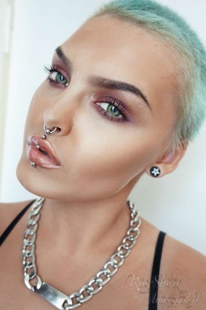 woman with pixie cut blue hair, green eyes, ashley piercing, septum ring piercing, nude lip gloss