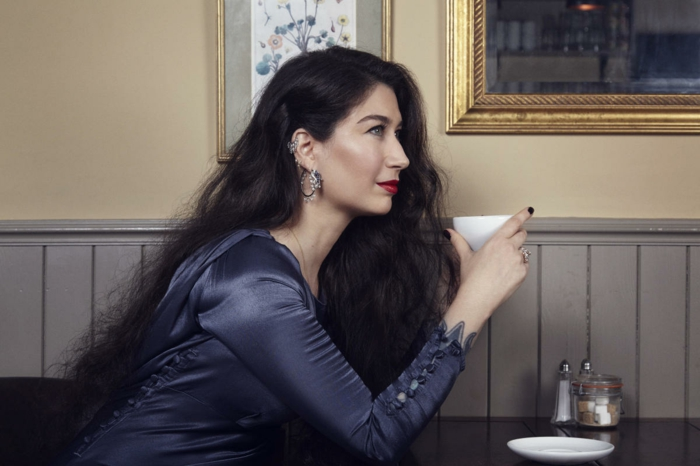 woman with long black wavy hair, wearing blue satin dress, double helix piercing, holding a coffee cup