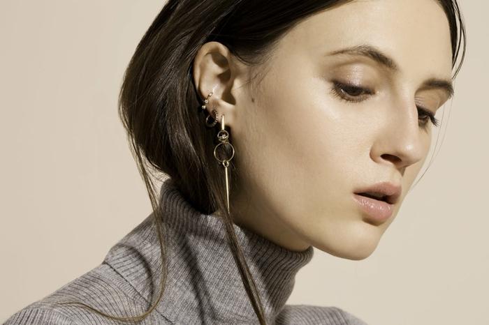 photo of brunette woman, wearing grey turtleneck blose, cartilage piercing, multiple earrings