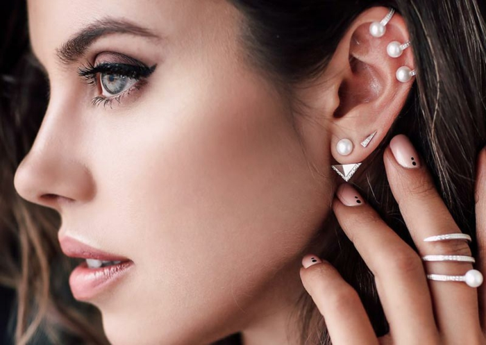 double cartilage piercing, woman with brown hair and green eyes, multiple earrings with pearls