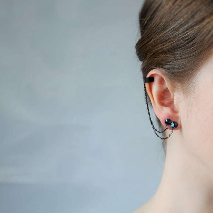 close up photo of an ear, woman with brown hair, cartilage ear piercings, black earrings connected with a chain