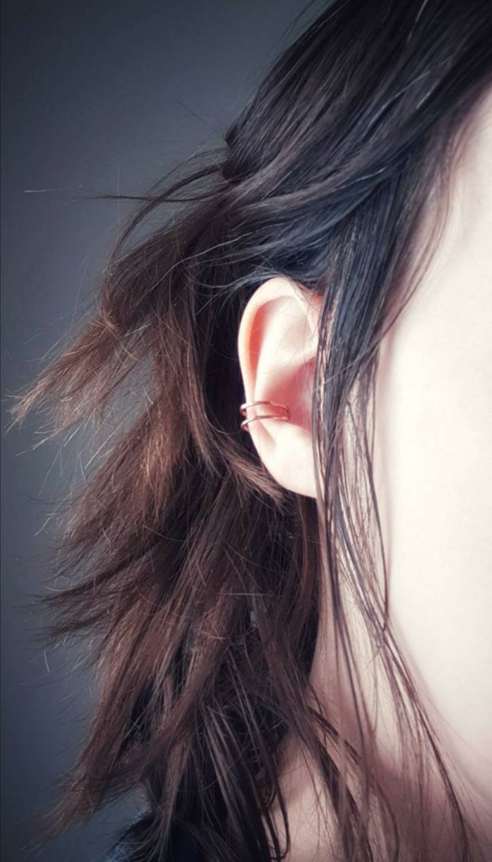 close up photo of an ear, woman with brown wavy hair, cartilage ear piercings, golden ring earrings