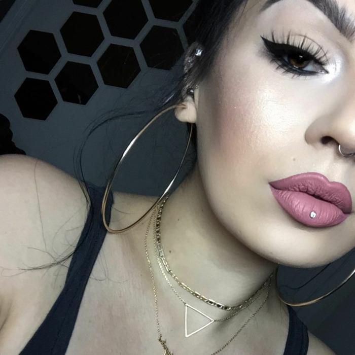 woman wearing large hoop earrings, labret piercing, pink matte lip gloss and black eyeliner