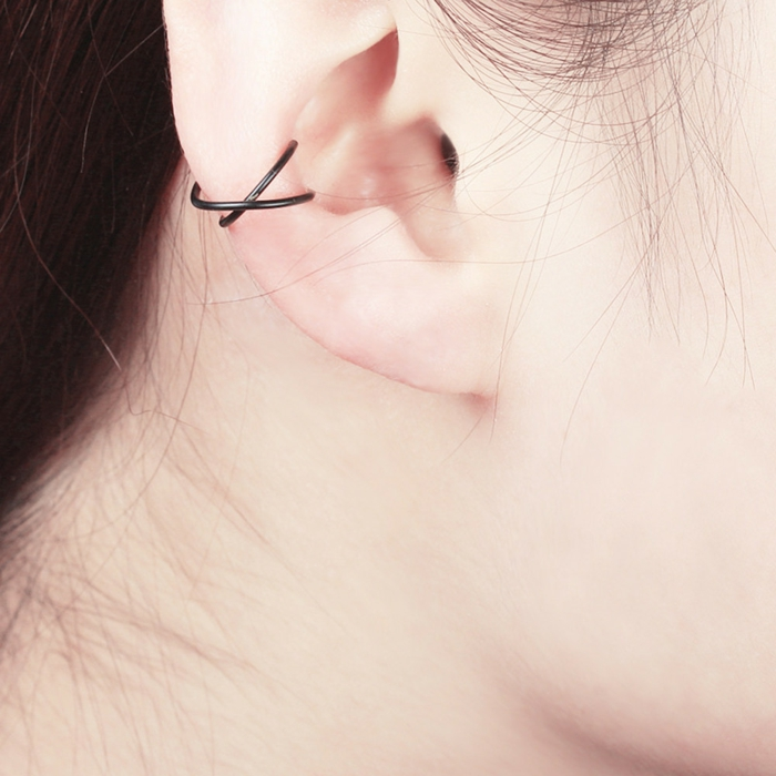 close up photo of an ear, woman with brown hair, forward helix piercing, two intertwining black ring earrings