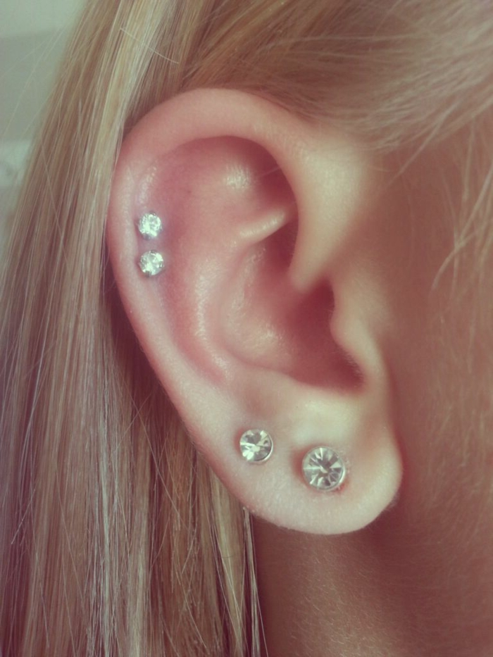 woman with blonde hair, wearing four earrings with rhinestones, forward helix piercing, close up photo