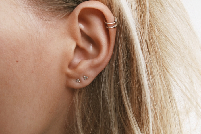 blonde woman, cartilage piercing, two silver ring earrings, two small stud earrings