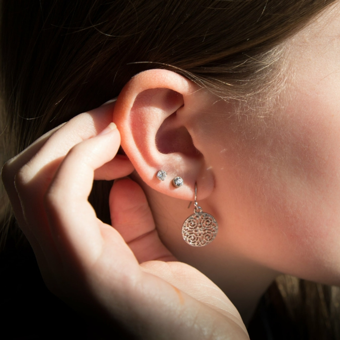 forward helix piercing, close up photo of an ear, woman with brown hair, wearing earrings with rhinestones