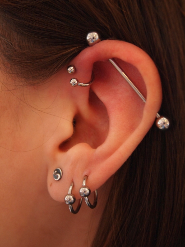 triple helix piercing, close up photo, woman with brown hair, multiple different silver earrings