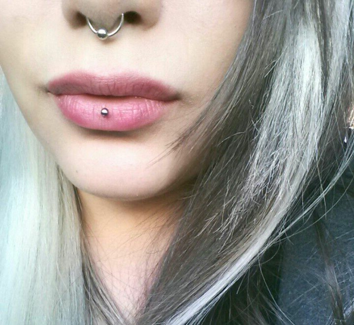 woman with ash blonde hair, lips with no lip gloss, middle lip piercing, septum ring piercing